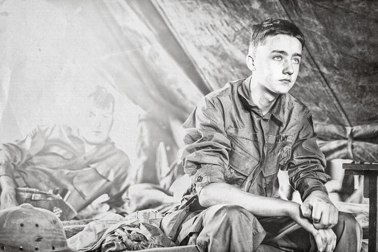 Young WWII Infantryman Sitting On A Cot In His Tent