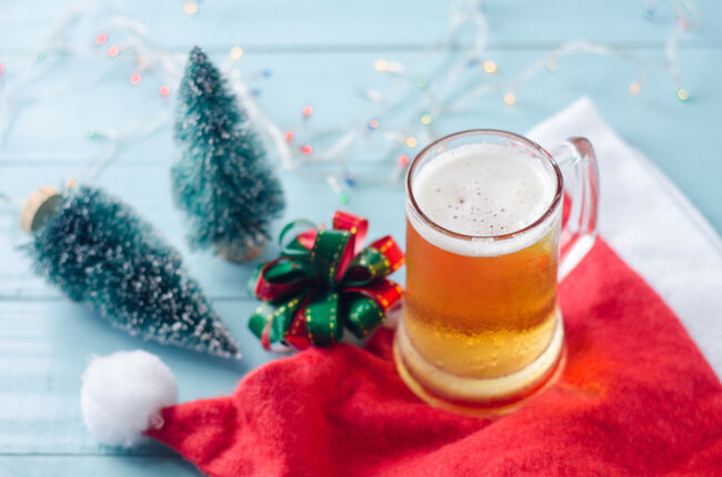 Glass of beer on christmas background with christmas tree, ribbon, santa claus hat and lights.