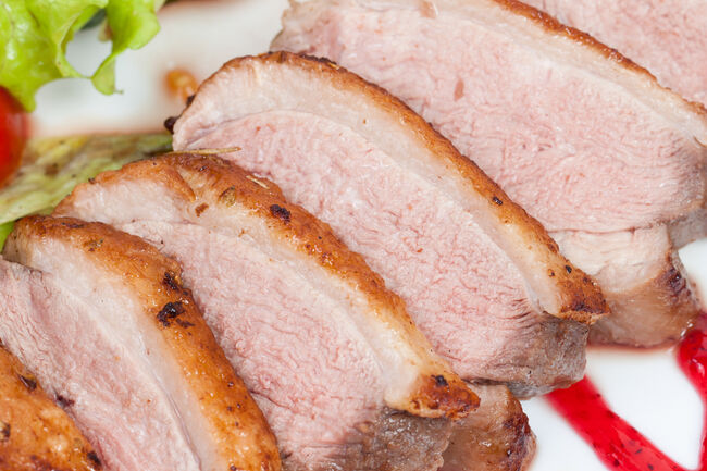 Glazed duck fillet, with salad on a white plate