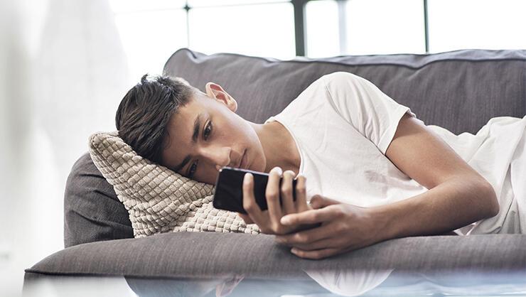 Teenage boy lying on sofa looking at smartphone