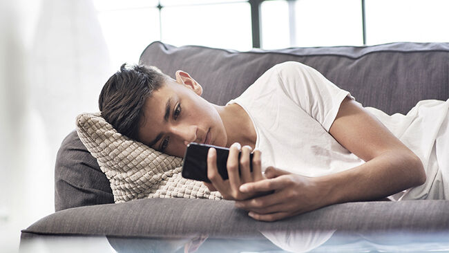 Teenage boy lying on sofa looking at smartphone