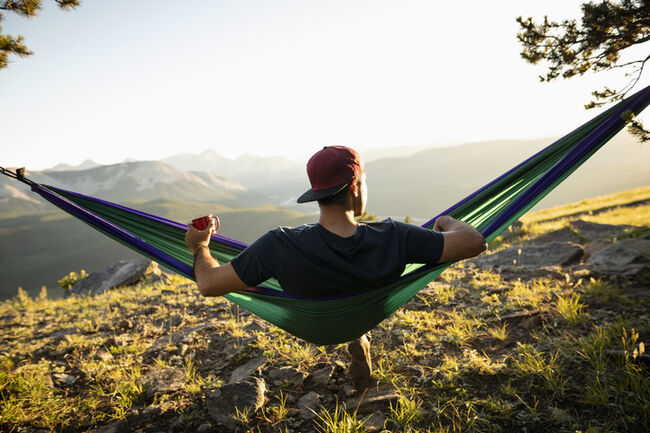 Serene man drinking coffee in sunny hammock with idyllic mountain view, Alberta, Canada
