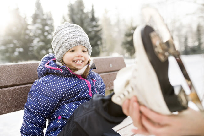 Mother helping daughter to put on her ice skates