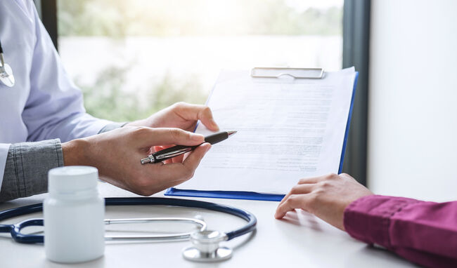 Midsection Of Doctor Showing Insurance Form To Patient