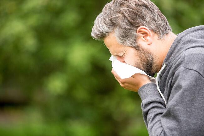 Man Sneezing By Tree