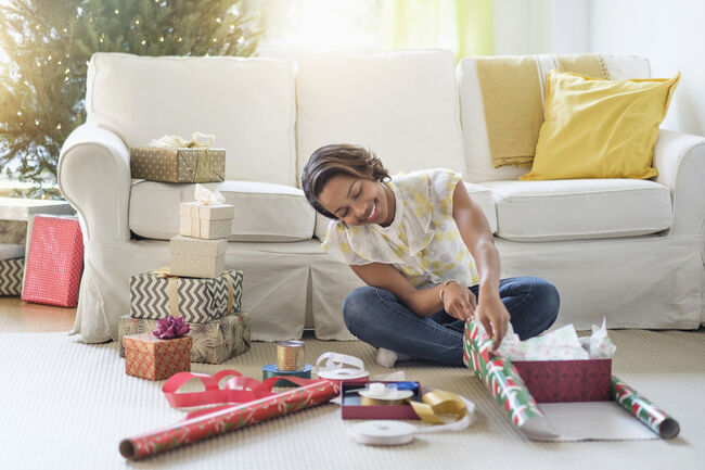 Black woman sitting on floor wrapping gifts
