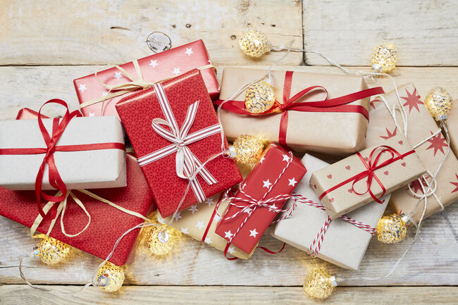 High angle view of a lot of wrapped Christmas gifts and strings lights on wooden background