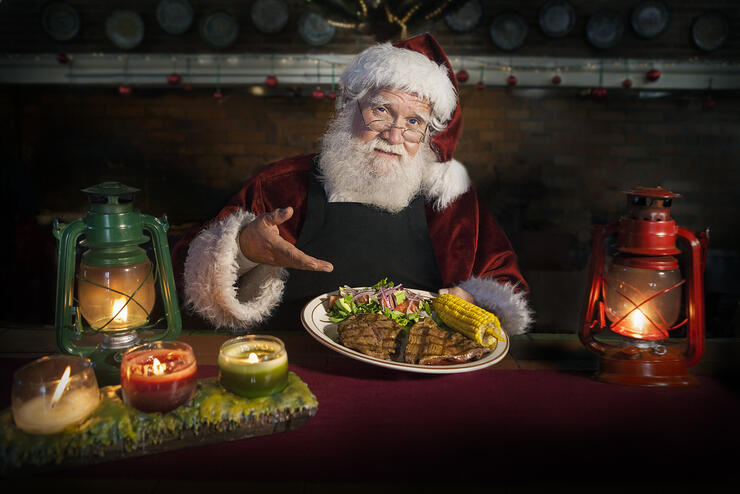 Chef Santa Claus holding a delicious grilled steak dish accompanied with corn and salad in a cozy kitchen counter lit by a candles and oil lamps