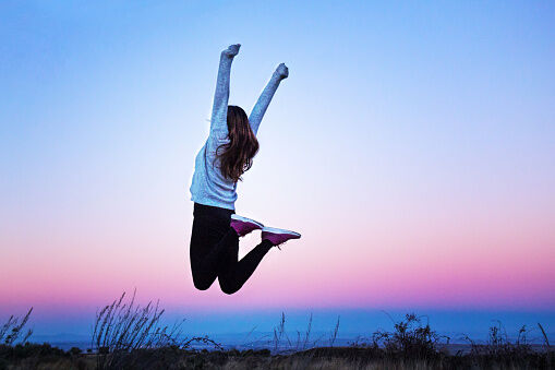 Young woman jumping raising her arms at a colorful sunset - Aragon, Spain