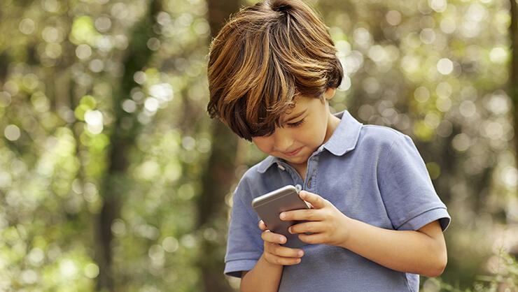 Smiling boy using mobile phone in forest