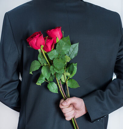 Elegant man holding red rose flowers in hand behind his back