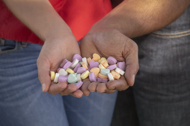 A young multiracial couple holds candy shaped hearts together on a sunny day during Valentine's day.