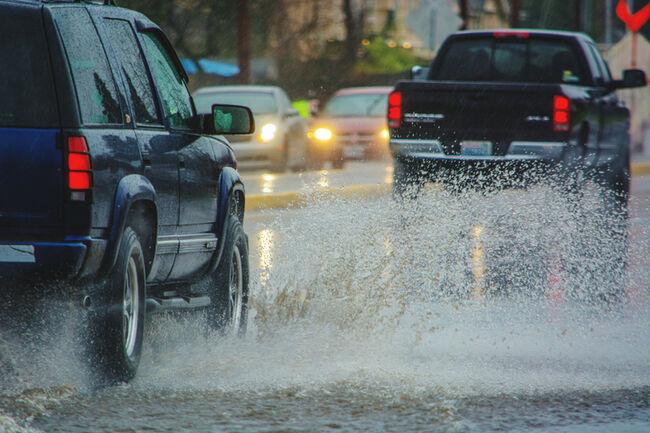 Cars Splashing Water On Road In Rainy Season