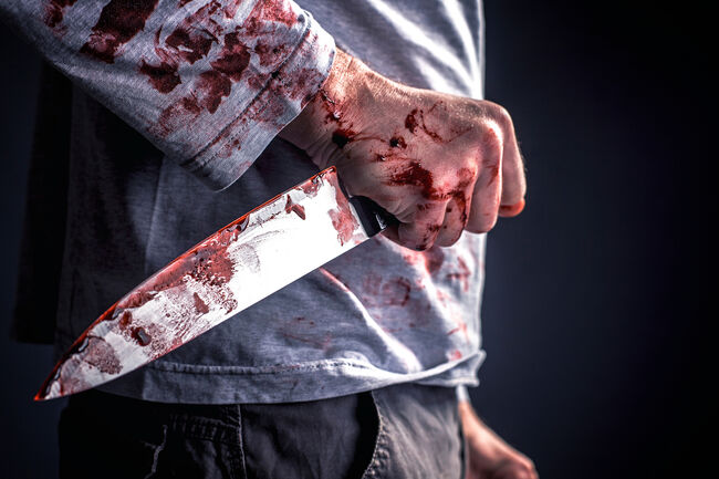 Midsection Of Murderer Holding Blooded Knife Against Black Background