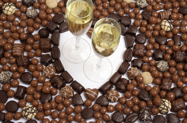 Heart shape created using chocolates with champagne glasses, elevated view, close-up