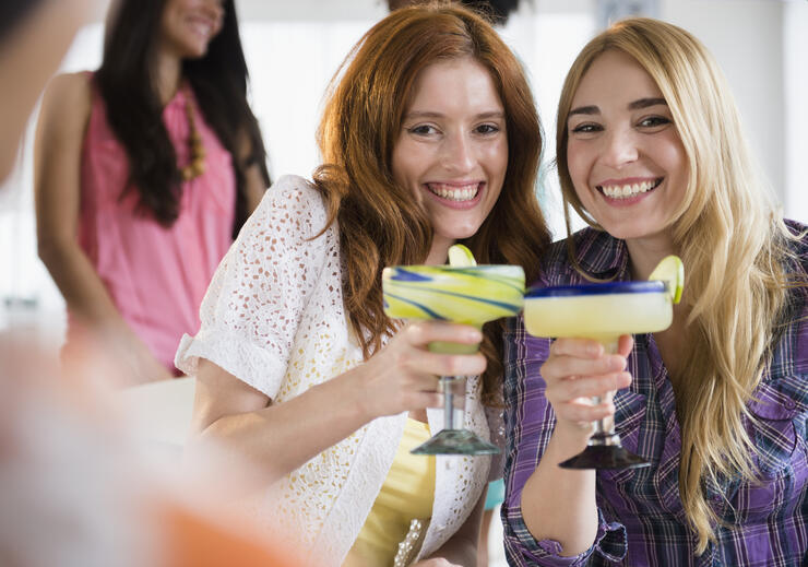 Women toasting each other with margaritas