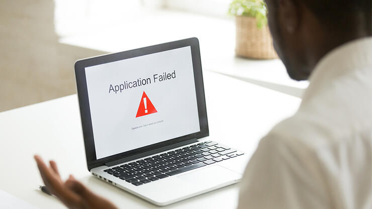 Frustrated worker getting virus notification at laptop scr