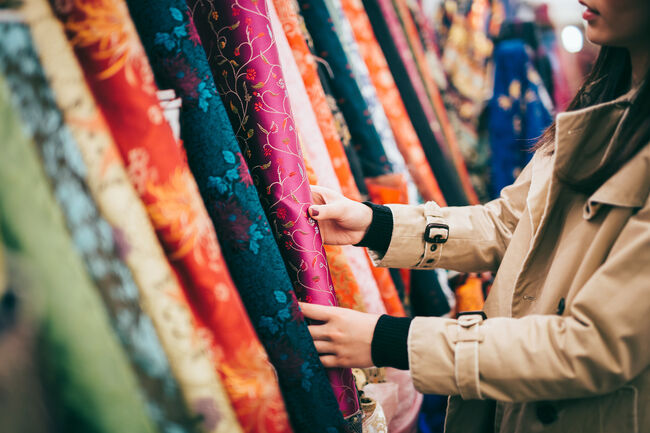 Fashion designer shopping for colourful fabrics in fabric store