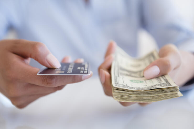 Hispanic woman holding cash and credit card