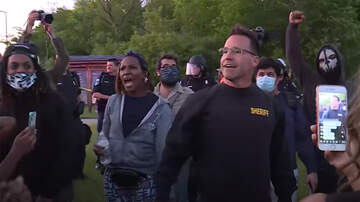 image for Michigan Sheriff Puts Down Baton, Joins Protesters Marching In Flint
