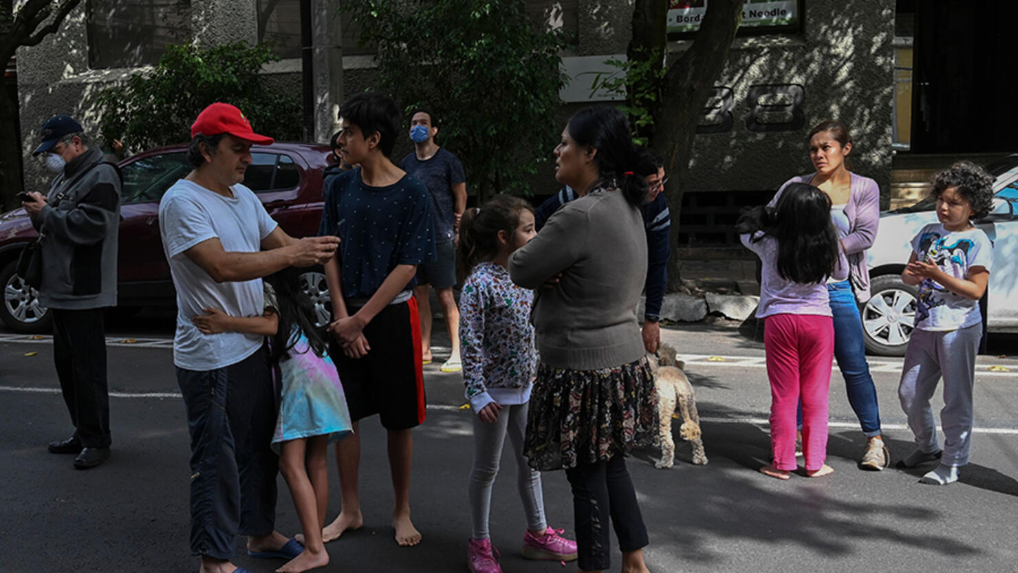 People are seen on a street during a quake in Mexico City, on June 23, 2020. - A 7.1 magnitude quake was registered Tuesday in the south of Mexico, according to the Mexican National Seismological Service. (Photo by RODRIGO ARANGUA / AFP) (Photo by RODRIGO