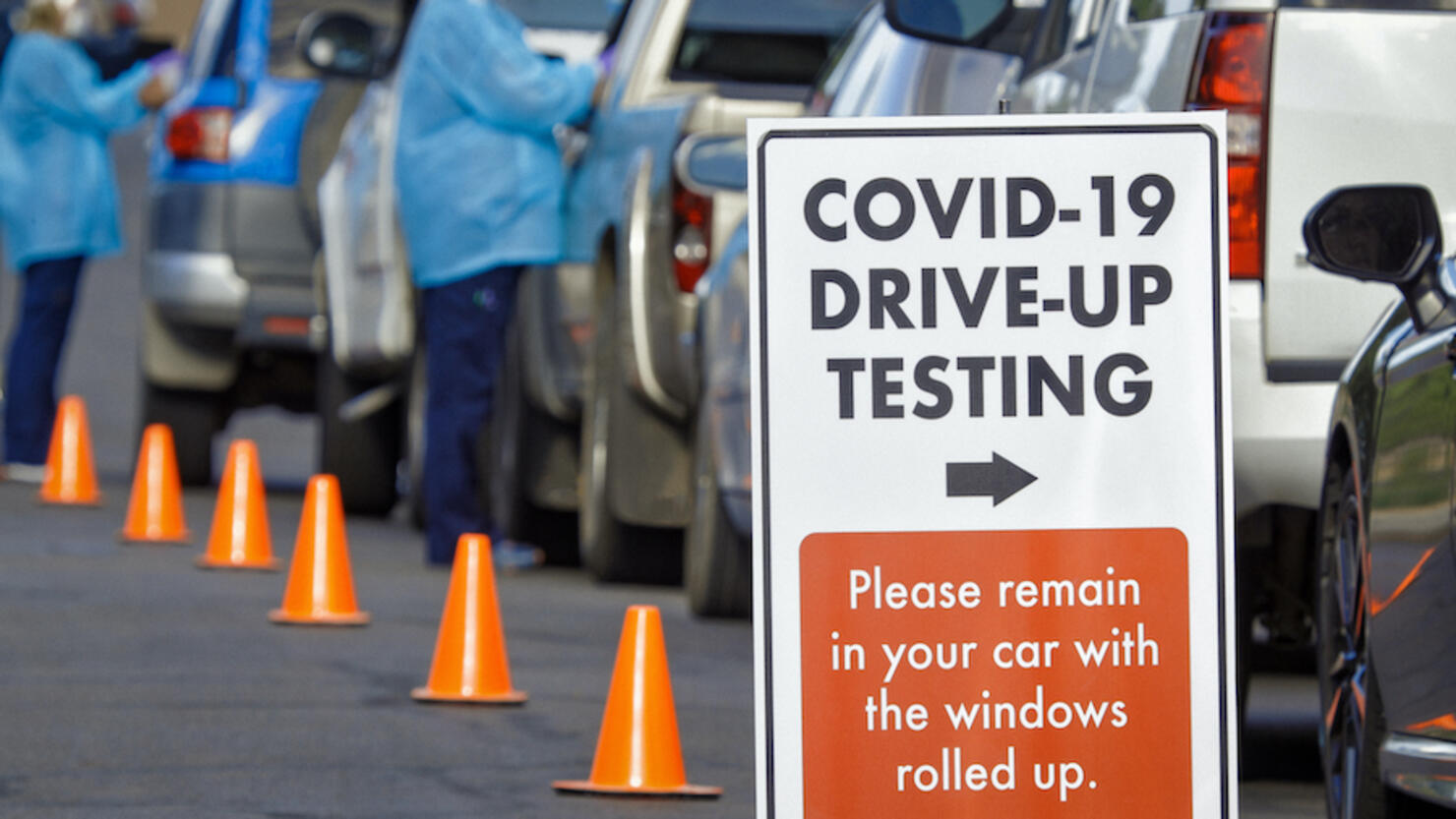 """A """"COVID-19 Drive-Up Testing"""" Sign Sits in the Foreground While Two Female Nurses Wearing Gowns and Surgical Face Masks Talk to Patients in their Cars in a Drive-Up (Drive Through) COVID-19 (Coronavirus) Testing Line Outside a Medical Clinic/Hospital Outd"""