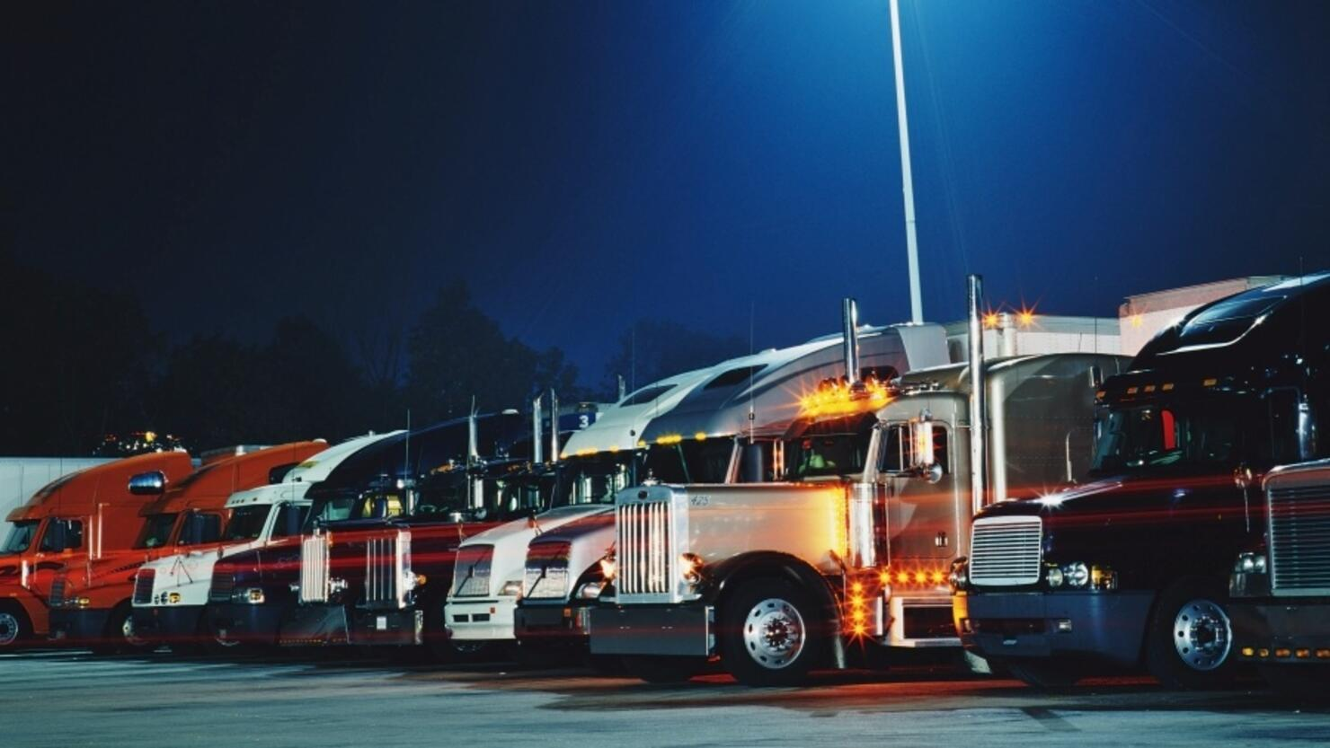 Semi-trucks in parking lot at night