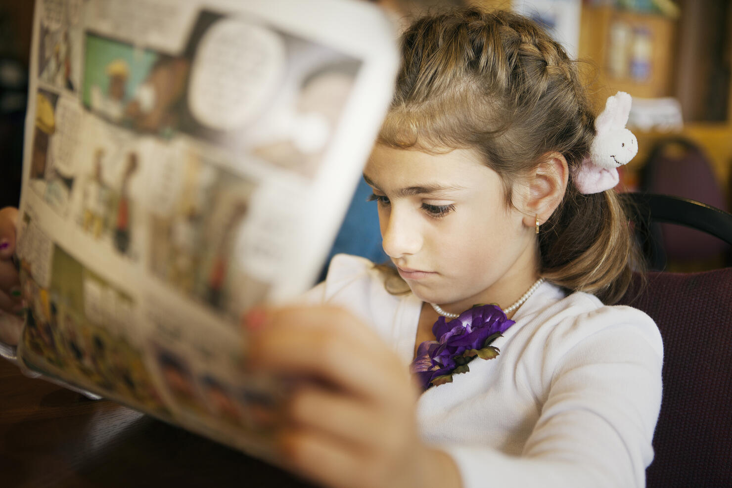 Mixed race girl reading newspaper