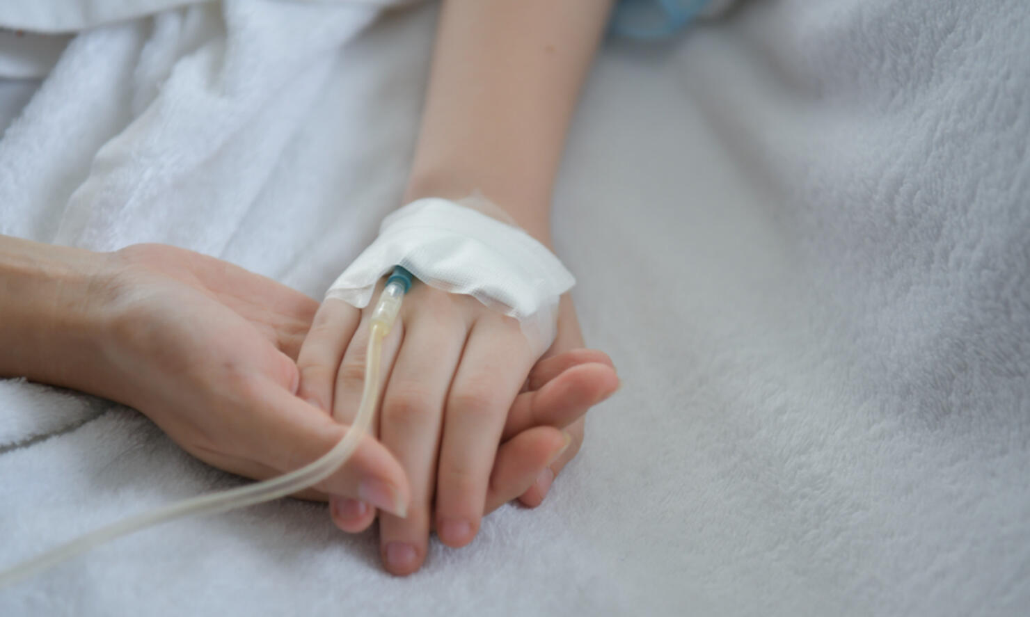 Close-Up Of Mother Holding Hands Of Medicated Child On Bed At Hospital