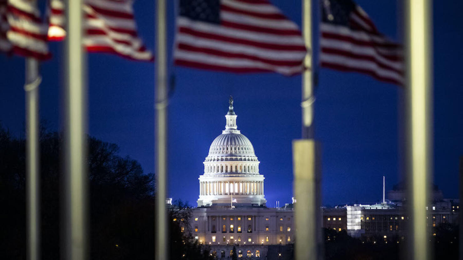 The U.S. Capitol is seen through American flags flying at half staff