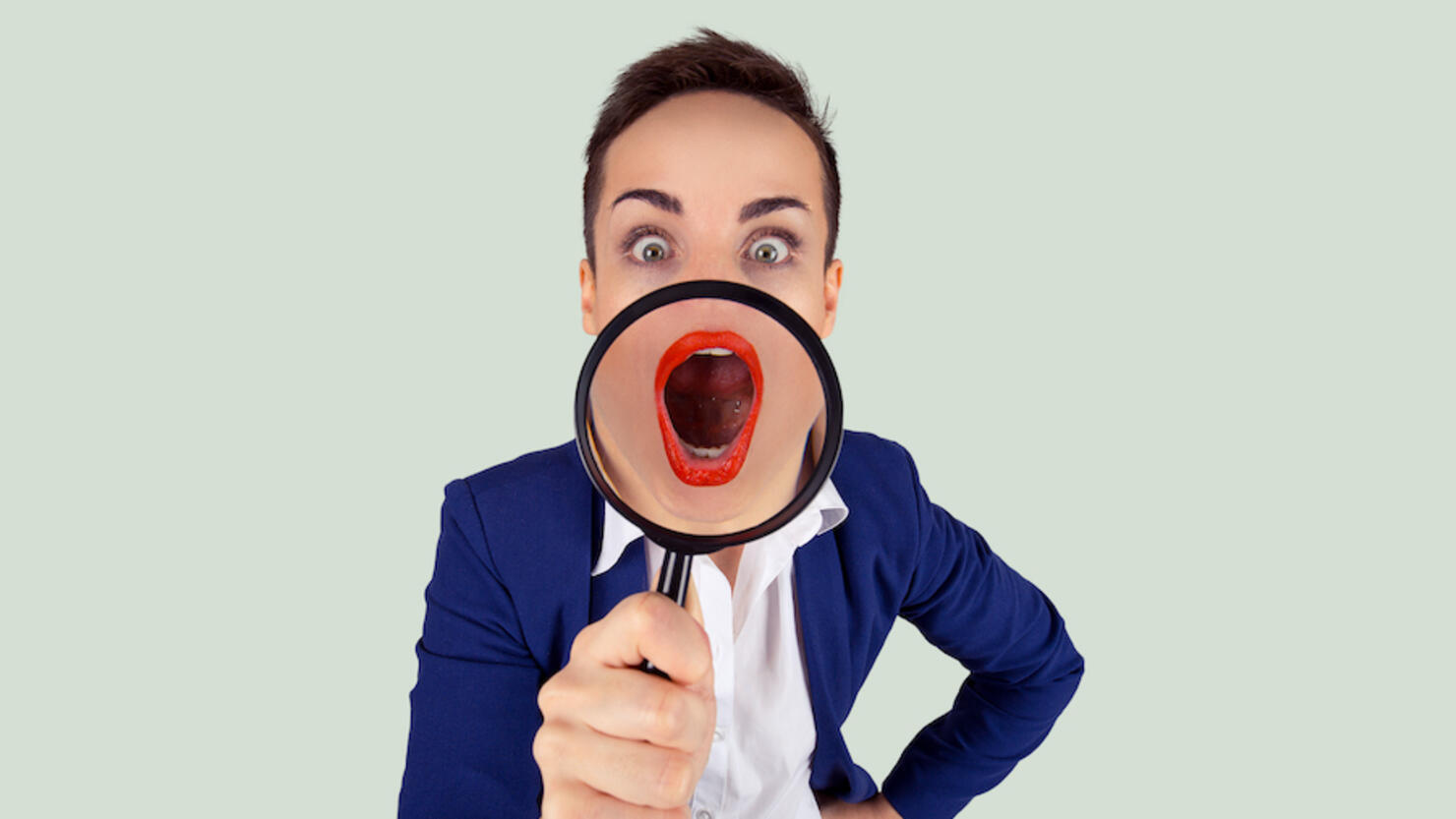 Wow, Big mouth open concept. Closeup cropped Portrait of a young shocked amazed young business woman blue suit  girl, magnifying lens on mouth isolated bright green white background Horizontal image